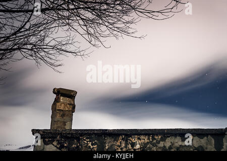 Night starry sky under a veil of white smoky clouds over the roof of an old abandoned house, beautiful nature near - Stock Photo