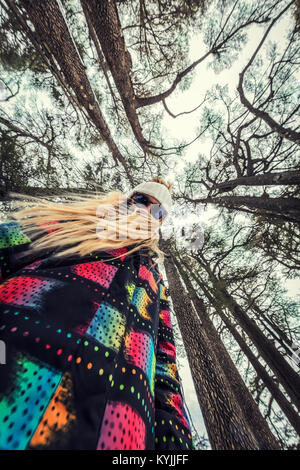 Perspective photo of a teen girl standing in the forest among giant Cedar trees, spending time outdoors in the nature, - Stock Photo