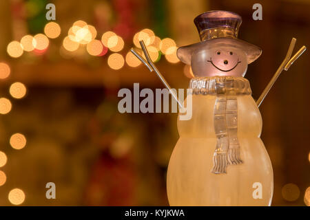 Winter Time Crystal Holiday Snowman in front of a fireplace mantle decorated for the holidays. - Stock Photo