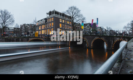 River cruise passing through under a canal bridge in Amsterdam during dusk - Stock Photo