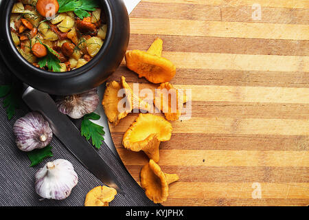 potatoes with mushrooms in a clay pot. Mushrooms from the forest - Stock Photo