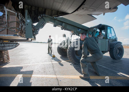 Senior Airman Judson Wisley, a loadmaster with the Kentucky Air National Guard's 165th Airlift Squadron, helps guide - Stock Photo