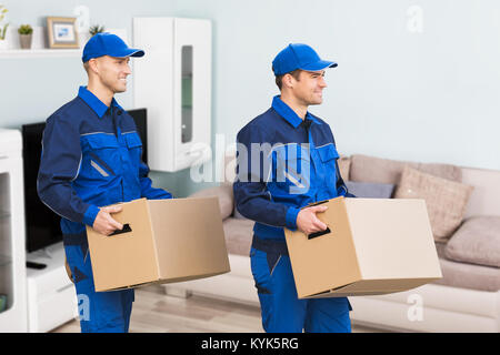 Young Smiling Professional Movers In Uniform Delivering Cardboard Boxes In Living Room - Stock Photo
