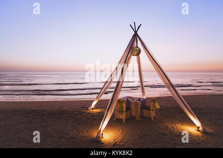 honeymoon dinner for wedding couple on the beach in luxurious romantic hotel, beautiful table for two at sunset - Stock Photo