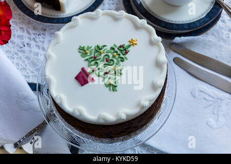 Fruit cake decorated on top with marzipan and royal icing and stencilled  Christmas Tree. - Stock Photo