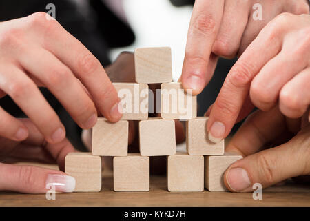 Close-up Of A People Arranging Block On Pyramid Over The Wooden Table - Stock Photo