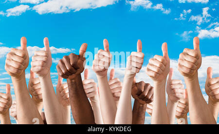 Many Hands Showing Thumb Up Sign Against Blue Sky - Stock Photo