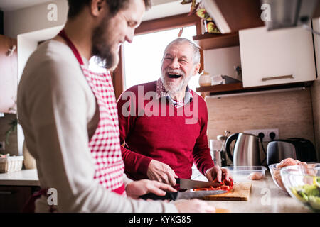 Hipster son with his senior father cooking in the kitchen. - Stock Photo