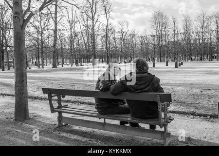 PARIS-Jan.3, 2014: Two men sit on a park bench talking on a winter day. Black and white. - Stock Photo