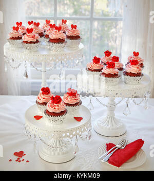 Cupcakes. Red velvet cupcakes decorated with red roses and hearts on 3 tier cakestand. - Stock Photo