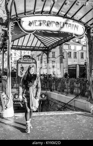 Paris, France. A beautiful woman at the entrance to the famous  art nouveau Metro subway station at the Abbesses - Stock Photo