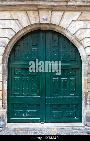 Paris France picturesque arched antique double front entry door, painted teal blue green. - Stock Photo