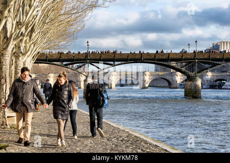 Paris, France, couples walk under old trees along the Seine River. Above is seen the famous bridge covered with - Stock Photo