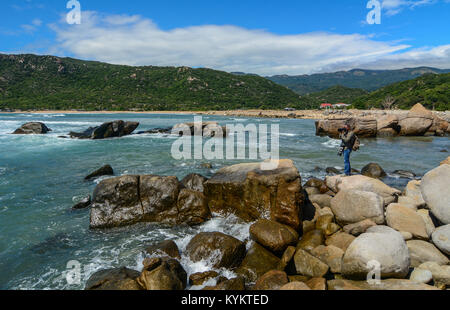 Nha Trang, Vietnam - Jan 27, 2016. A photographer standing on rocks and looking at beautiful sea in Nha Trang, South - Stock Photo