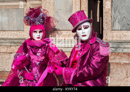VENICE, ITALY - FEBRUARY 18, 2017: Unidentified participants wear vintage colorful costumes and white masks during - Stock Photo