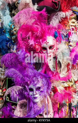 Ornate carnival masks among colorful feathers in Venice, Italy. - Stock Photo