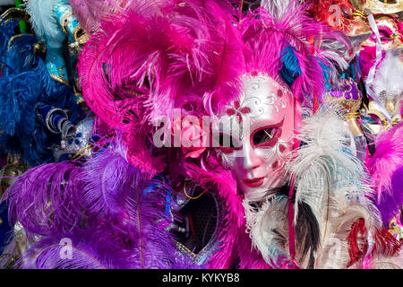 Ornate carnival mask among colorful feathers in Venice, Italy. - Stock Photo
