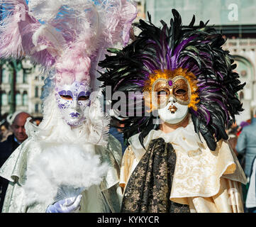 VENICE, ITALY - FEBRUARY 18, 2017: Two unidentified participants wear traditional vintage costumes and masks with - Stock Photo