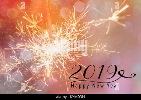 Sparklers against a pink backdrop with bokeh and falling snow effect. Happy New Year 2019 quote. - Stock Photo