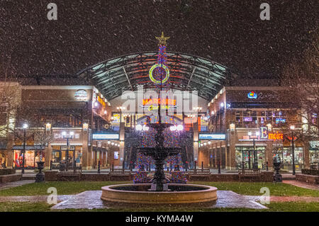The first snow in Huntington, West Virginia of 2017 hits Pullman Square, the fountain and streets adorned with Christmas - Stock Photo
