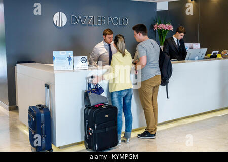 Buenos Aires Argentina Palermo Dazzler Polo hotel lobby front-desk clerk man woman couple guest luggage Hispanic - Stock Photo