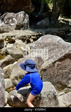 Young girl crosses a dry river bed with massive rocks in a rainforest, Finch Hatton Gorge, Queensland, Australia - Stock Photo