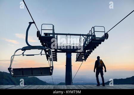 Tourist man walking at ski lift station in silhouette high in mountain ski resort at sunrise - Stock Photo