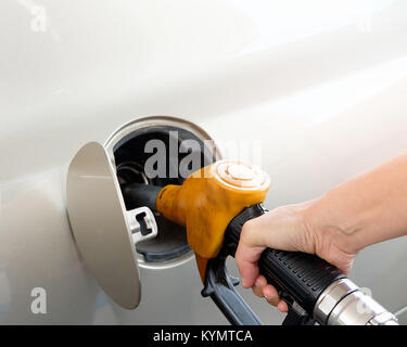 The gold car is filling the fuel at the oil station. Hand holding Fuel nozzle in gas pump. - Stock Photo