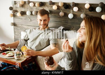 Couple having breakfast in bed - Stock Photo