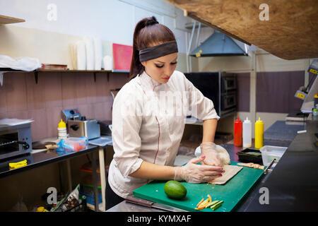 female chef preparing a sushi restaurant in the kitchen - Stock Photo