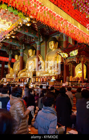 Devotees praying at the Jogyesa Buddhist Temple, Jongno-gu, Seoul during a religious ceremony - Stock Photo