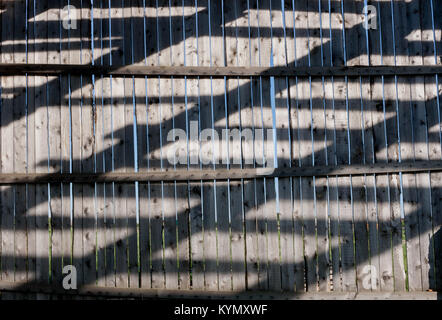 Old wooden grey fence made of boards with diagonal pattern of solar and shadow strips on them. - Stock Photo