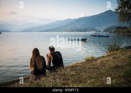 Tourists on the bank of the Phewa Lake in Pokhara, Nepal, Asia. - Stock Photo