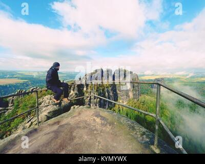 Hiker man take a rest on mountain peak. Man sit on summit view point, bellow cloudy  valley. Bright morning Sun - Stock Photo