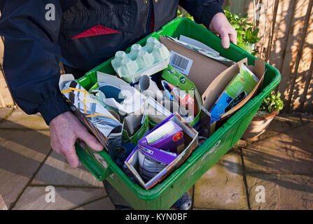Close up of man putting out carrying recycling box recycle waste paper and cardboard boxes for collection England - Stock Photo