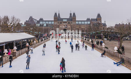 Amsterdam, Netherlands - January 04 2018: Public enjoying the winter by iceskating outdoor in front of the Iamsterdam - Stock Photo