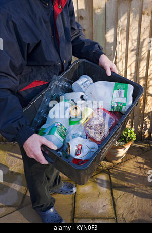 Man putting out plastic and tins recycling box for collection England UK United Kingdom GB Great Britain - Stock Photo
