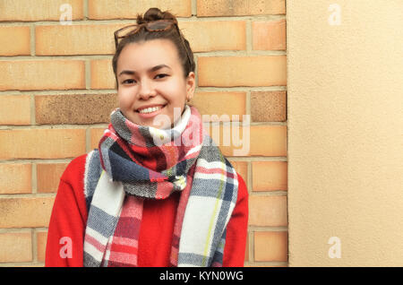 A beautiful Asian woman standing against a brick wall. Wrapped in a scarf. On the head of the glasses - Stock Photo