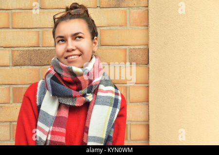 An attractive and young Asian woman with her hair tied to the knot, stands at the brick wall and looks thoughtfully - Stock Photo