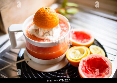 juicer with citrus fruit squeezed in the kitchen citrus juice vitamin - Stock Photo
