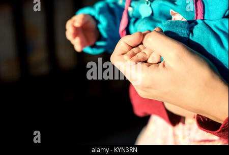 Caucasian woman's hands holding the hand of her white baby in natural sunlight with defocused background and copy - Stock Photo