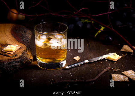 Glass of whiskey with ice cubes served on wooden table. Vintage countertop with grapes, crackers  and a glass of - Stock Photo