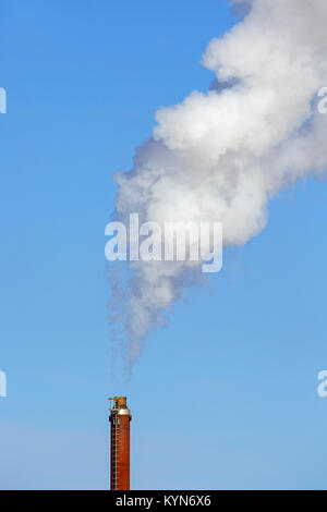 Industrial chimney / smoke stack / smokestack against blue sky on a windless day - Stock Photo