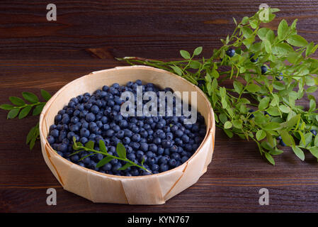 Blueberries in a wicker basket on wooden table - Stock Photo