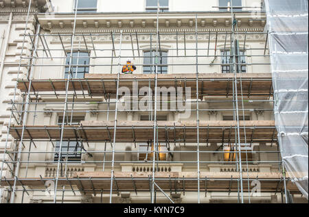 Workman in hard hard and safety clothing, standing on a scaffolding platform, outside a multi storey property. South - Stock Photo