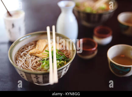 Bowl of Ramen with Soba noodles and tofu on a table in a Japanese restaurant, Kyoto, Japan. - Stock Photo