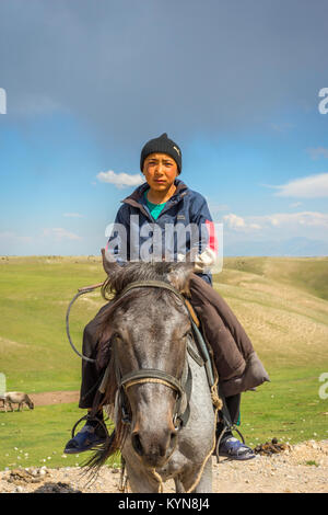 KAZARMAN, KYRGYZSTAN - AUGUST 14: Local guy wearing a hat sitting on a horse in remote Kyrgyzstan. August 2016 - Stock Photo
