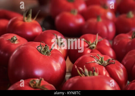 Ripe, red, organic, homegrown heritage variety tomatoes fill the frame, with side lighting and selective focus on - Stock Photo