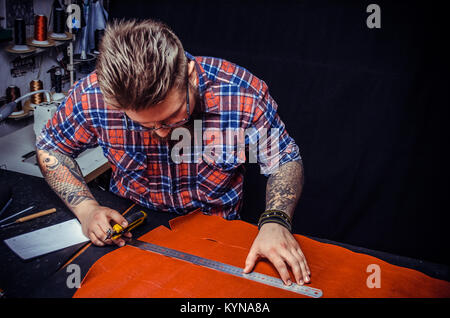 Leather Artist creating new leatherwork - Stock Photo