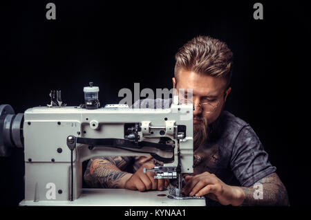 Leather Worker at work on his new leather product - Stock Photo